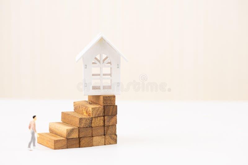 Piccola figura della gente miniatura che cammina per modellare casa bianca sul blocco di legno che impila la scala di punto Inves fotografia stock libera da diritti