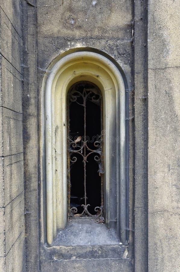 Piccola finestra della griglia in parete di pietra immagine stock