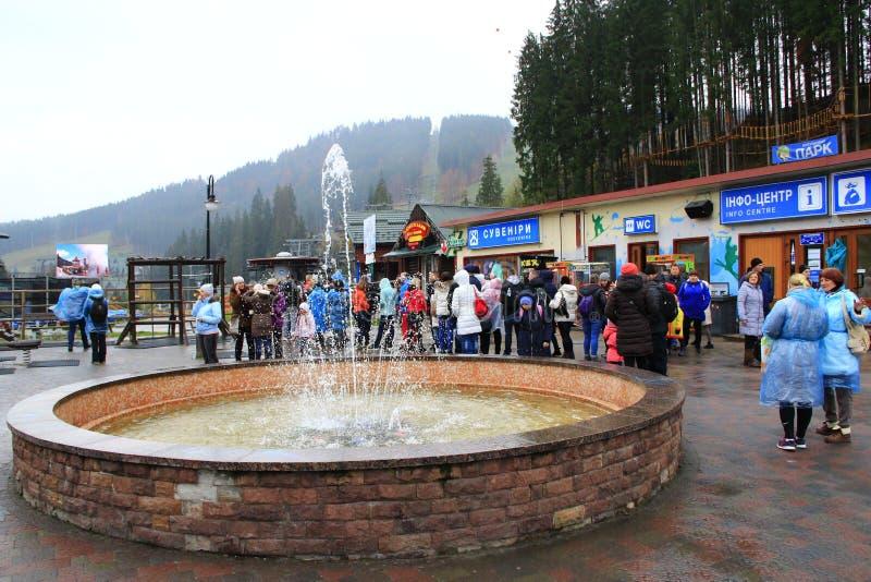 Piccola fontana in Bukovel in montagne carpatiche La gente che ha un resto in stazione turistica fotografie stock libere da diritti