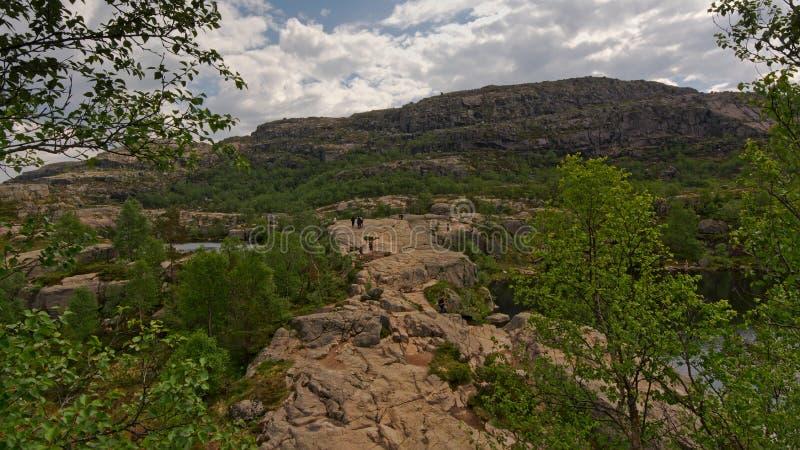 Piccola gente che fa un'escursione su un grande plateau della montagna in Rogaland, Norvegia fotografia stock libera da diritti