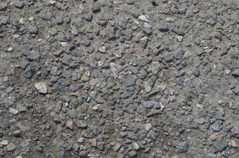 Piccola ghiaia nell'asfalto grigio immagine stock