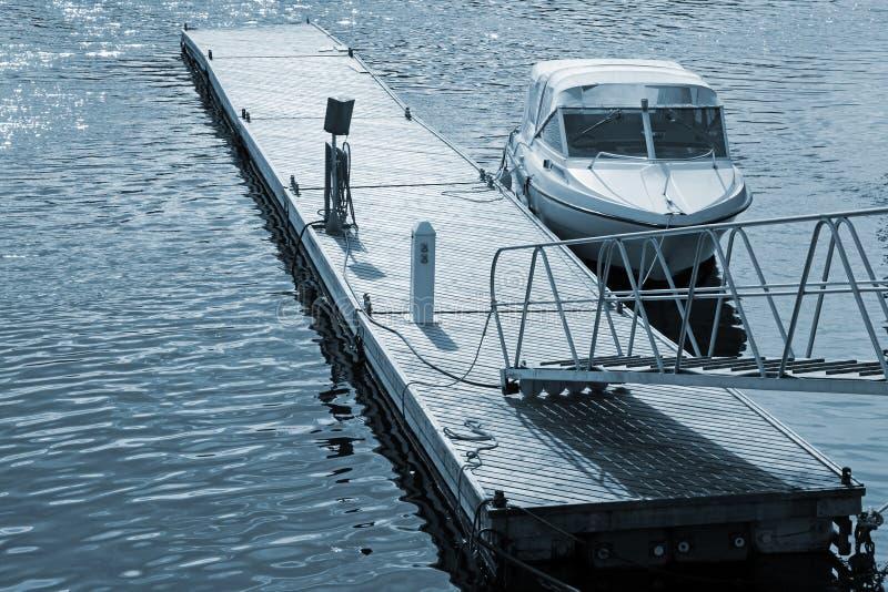 Piccola imbarcazione a motore vicino che fa galleggiare pilastro di legno immagini stock libere da diritti