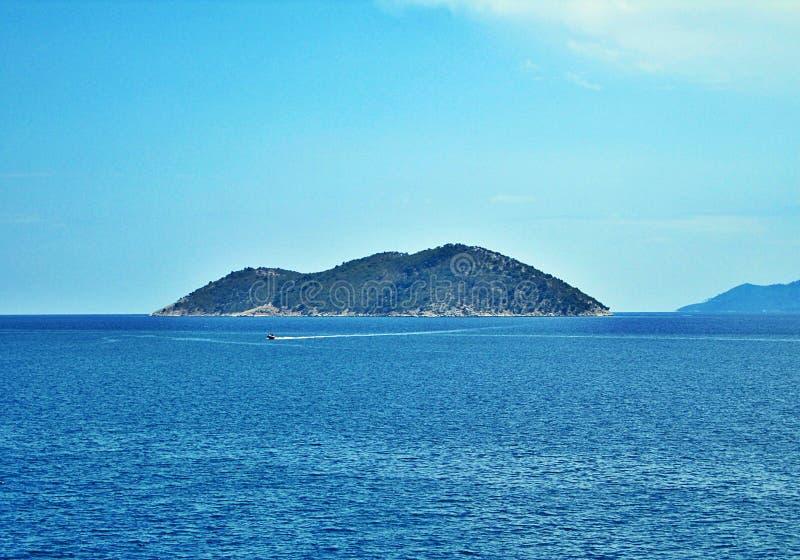 piccola isola in mezzo ad un pezzetto un giorno soleggiato Grecia fotografia stock libera da diritti