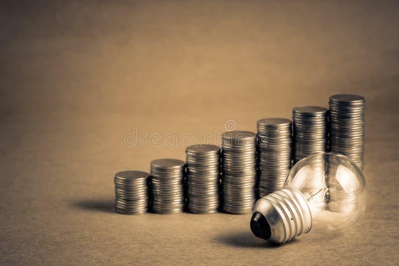 Piccola lampadina con la scala delle monete fotografia stock