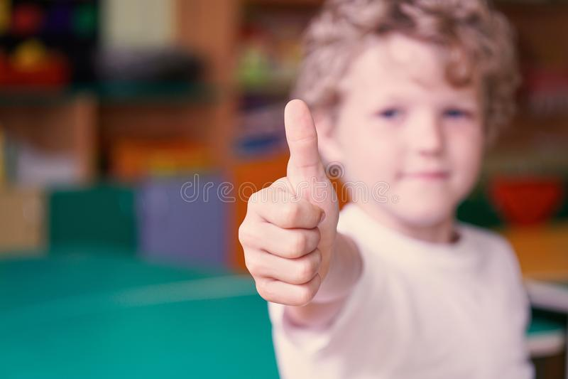 Piccola manifestazione riccia del ragazzo il suo pollice su Immagine con profondità di campo fotografia stock