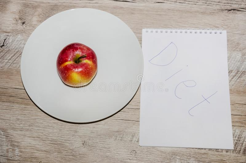 Piccola, mela rossa su un piatto bianco e un blocco note su una tavola grigia e di legno immagini stock libere da diritti