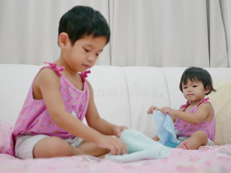 Piccola neonata asiatica, 18 mesi, i suoi vestiti pieganti e prova della sorella più anziana per fare la stessa cosa immagini stock