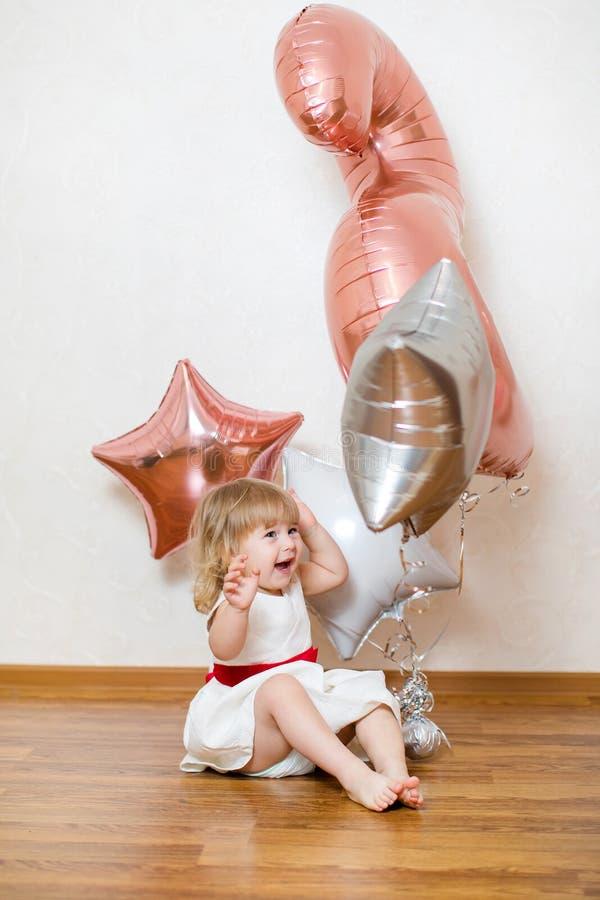 Piccola neonata bionda due anni con i grandi palloni bianchi e di rosa sulla sua festa di compleanno immagini stock