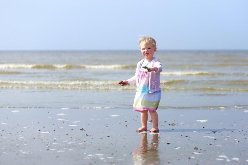 Piccola neonata che gioca sulla spiaggia immagini stock
