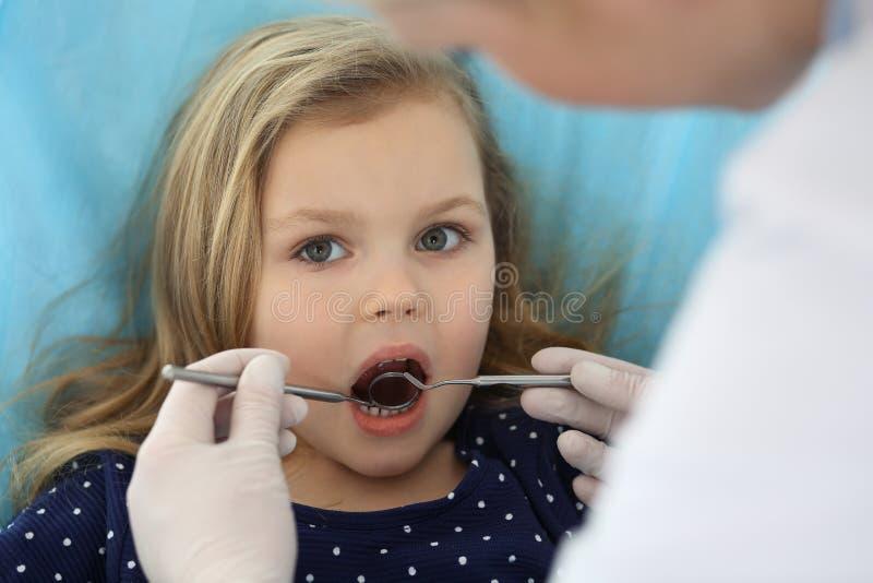 Piccola neonata che si siedono alla sedia dentaria con la bocca aperta e timore ritenente durante il controllo orale su medico di immagini stock