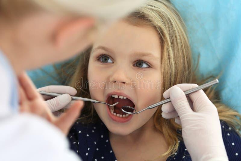 Piccola neonata che si siedono alla sedia dentaria con la bocca aperta e timore ritenente durante il controllo orale su medico di fotografia stock libera da diritti