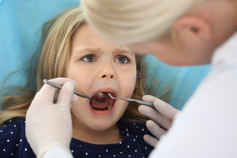 Piccola neonata che si siedono alla sedia dentaria con la bocca aperta e timore ritenente durante il controllo orale su medico di immagine stock