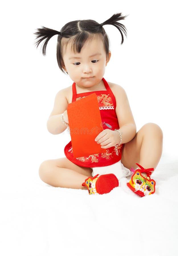 Piccola neonata che tiene una busta rossa per il nuovo anno cinese fotografie stock libere da diritti