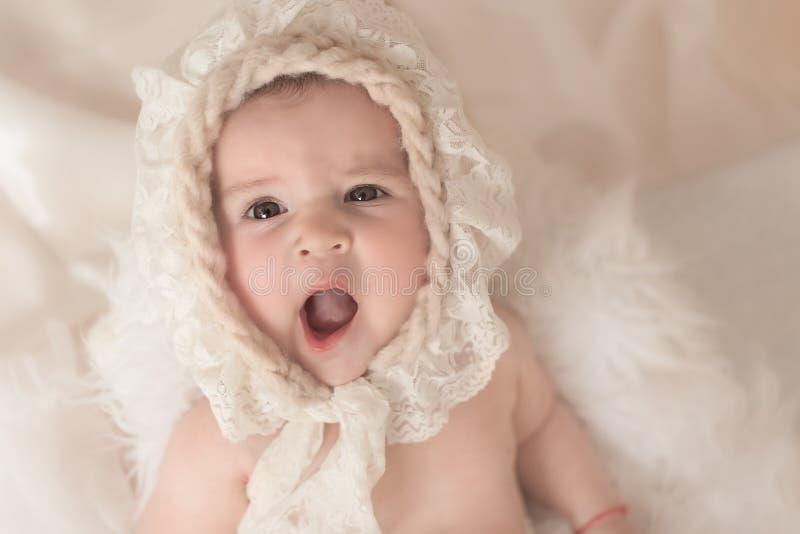 Piccola neonata con il cappello che sbadiglia fotografie stock