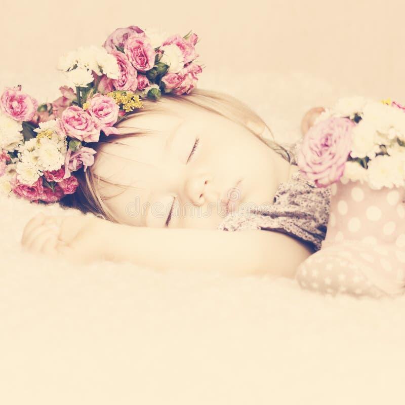 Piccola neonata dolce che dorme in Rose Flowers rosa Vint tonificato fotografia stock libera da diritti