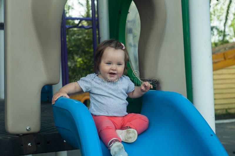 Piccola neonata felice che rotola giù la collina sul campo da giuoco immagine stock libera da diritti
