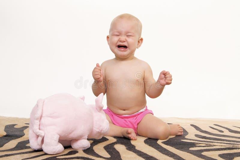 Piccola neonata gridante sulla pelle artificiale della zebra immagini stock