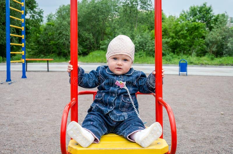 Piccola neonata in jeans e nella guida del cappello su un'oscillazione al campo da giuoco fotografia stock