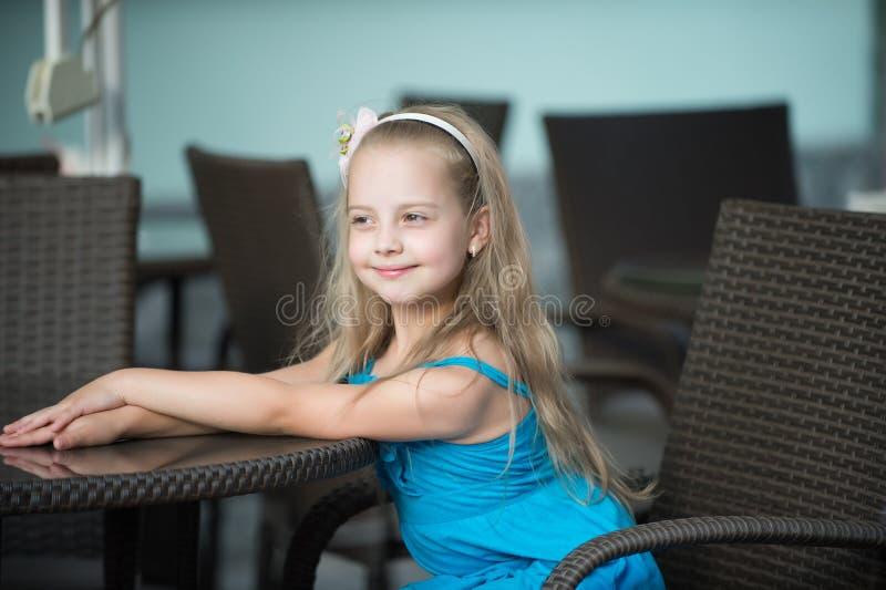 Piccola neonata sorridente in vestito blu vicino alla tavola del caffè fotografie stock libere da diritti