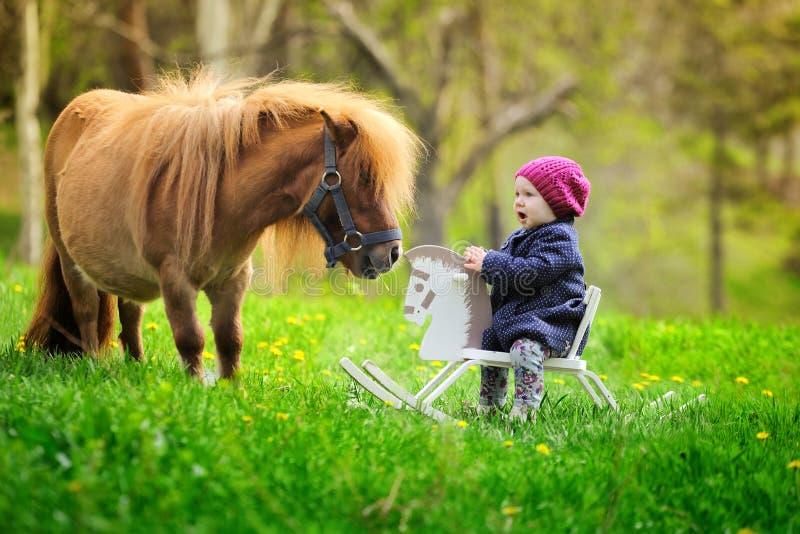 Piccola neonata sul cavallo a dondolo e sul cavallino di legno immagine stock