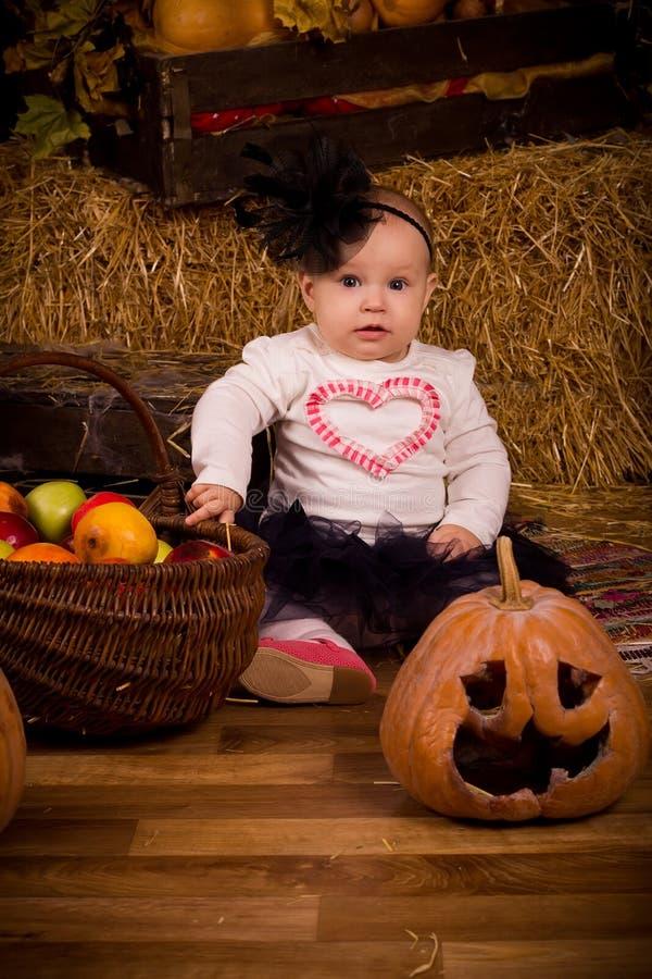 Piccola neonata sul partito di Halloween con la zucca fotografie stock libere da diritti