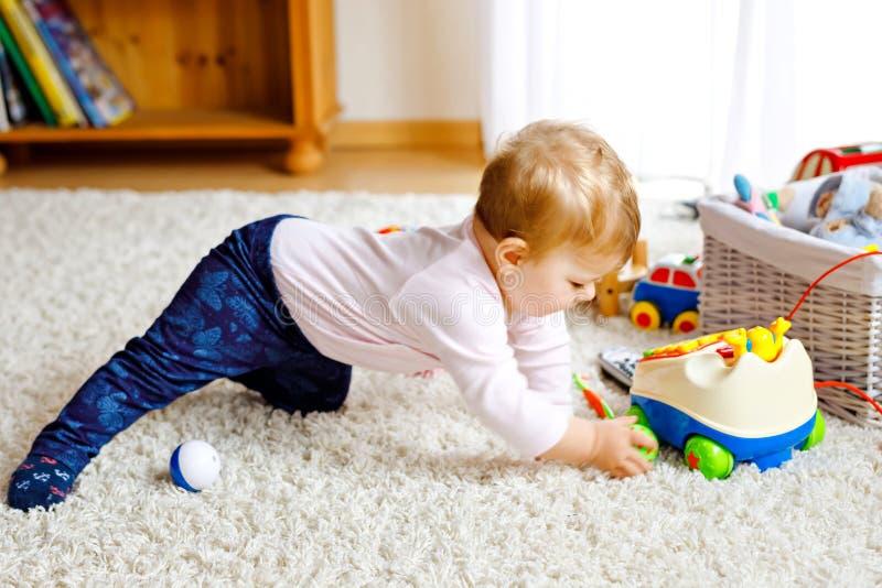 Piccola neonata sveglia che impara strisciare Bambino in buona salute che striscia nella stanza dei bambini con i giocattoli vari fotografie stock