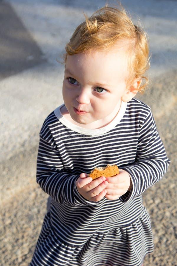Piccola neonata sveglia con i biscotti fotografia stock