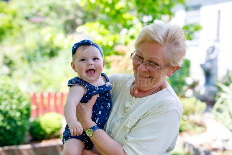 Piccola neonata sveglia con la nonna il giorno di estate in giardino immagini stock