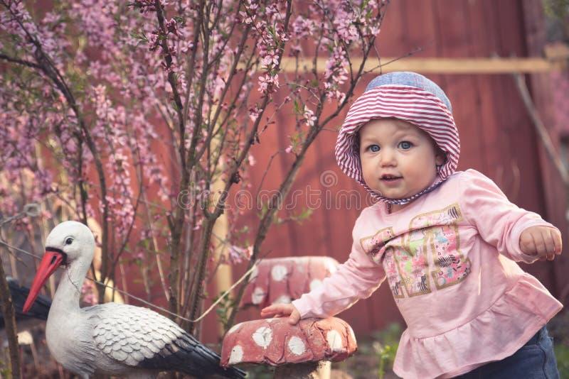 Piccola neonata sveglia in vestito rosa che possing per la macchina fotografica nel parco immagine stock