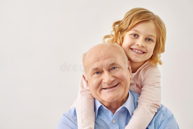 Piccola nipote che abbraccia suo nonno fotografia stock