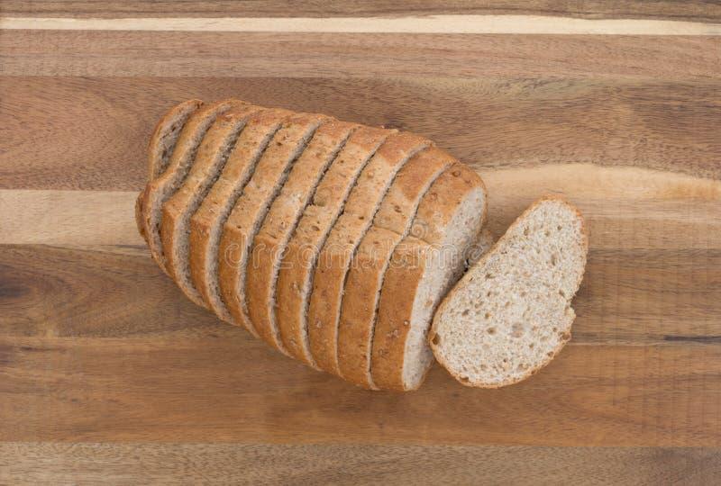 Piccola pagnotta di pane integrale affettato su un tagliere fotografie stock libere da diritti