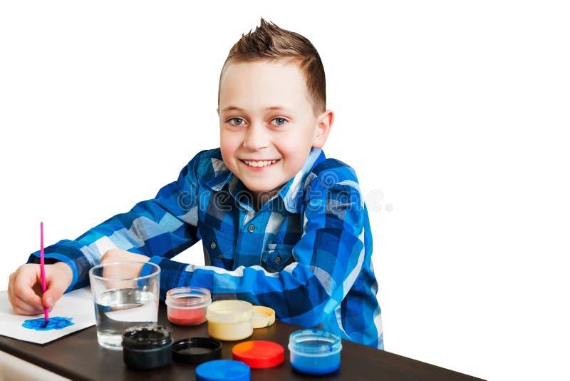 Piccola pittura del bambino con la gouache Ritratto della spazzola della tenuta del ragazzo e pittura su Libro Bianco Isolato su  immagine stock