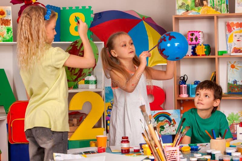 Piccola pittura della ragazza degli studenti sul pallone nella classe di scuola di arte immagine stock libera da diritti