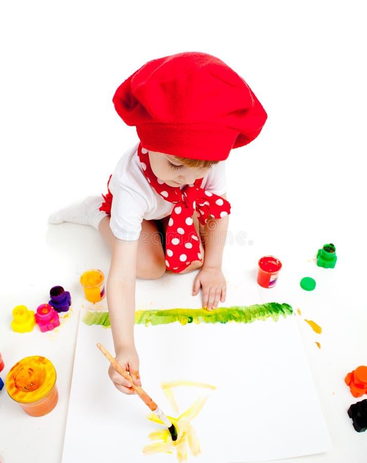 Piccola pittura della ragazza del bambino dell'artista con la spazzola fotografia stock