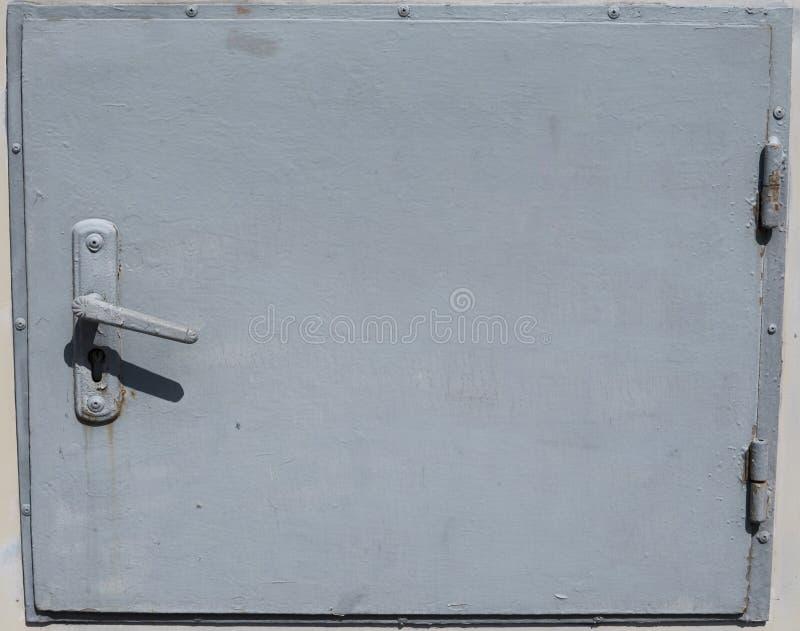 Piccola porta del metallo del gabinetto metallico inbuilded sulle pareti esterne immagine stock