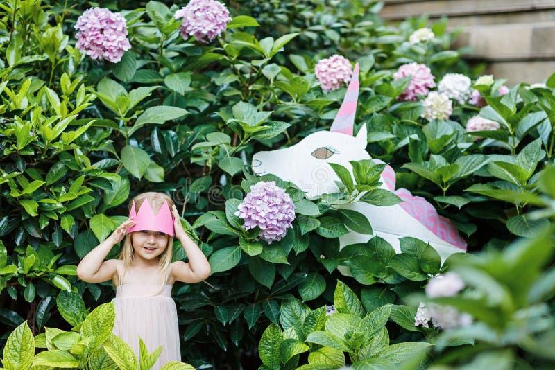 Piccola principessa con l'unicorno del giocattolo Una piccola principessa felice usa la sua immaginazione per posare con il suoi  immagine stock