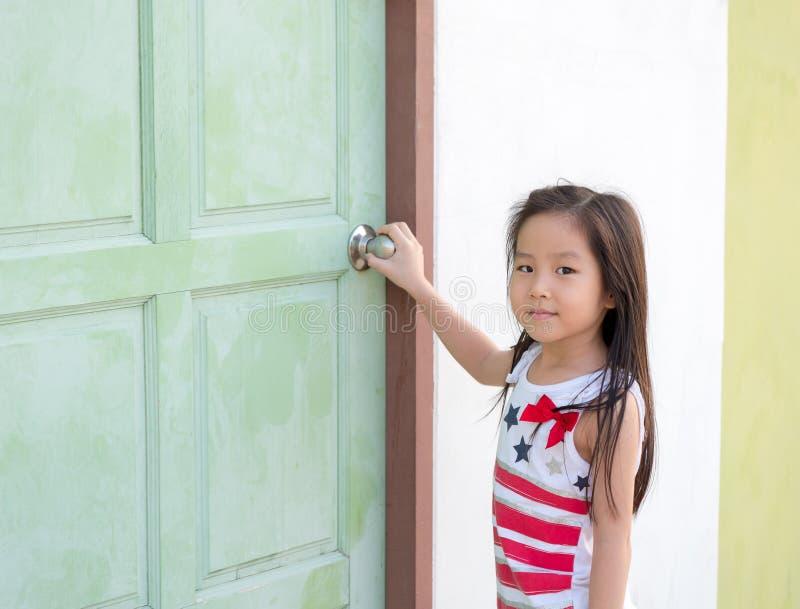 Piccola prova asiatica del bambino della ragazza per aprire la porta fotografia stock libera da diritti