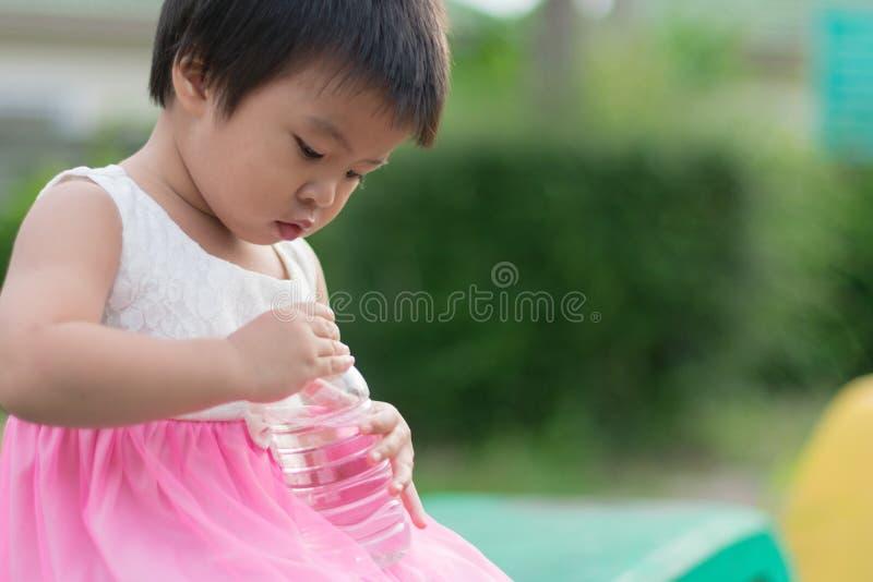 Piccola prova sveglia asiatica della ragazza per chiudere la bottiglia di plastica di pulito fotografia stock libera da diritti