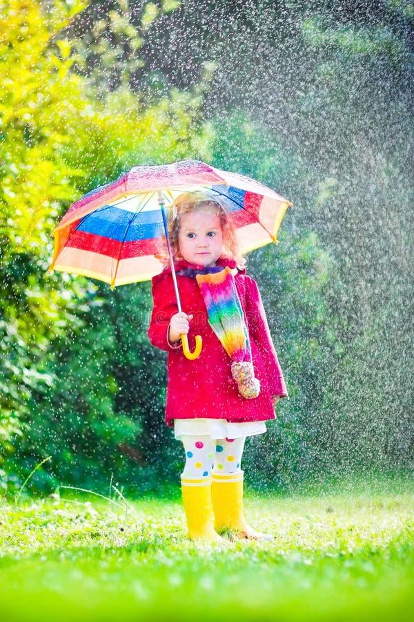 Piccola ragazza adorabile che gioca nella pioggia fotografia stock libera da diritti