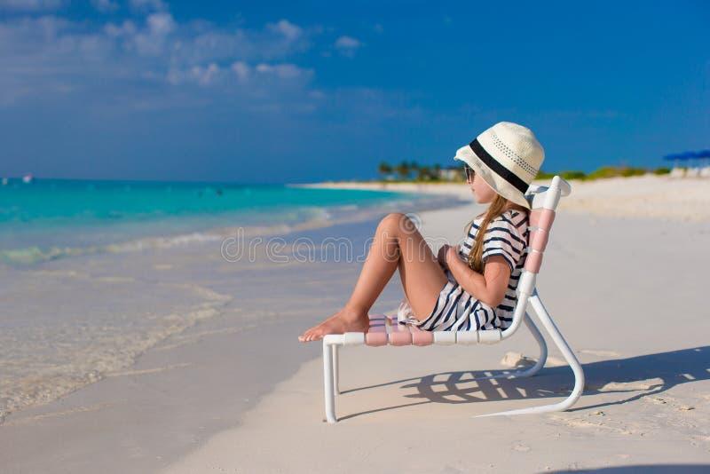 Piccola ragazza adorabile nella sedia di spiaggia durante immagini stock
