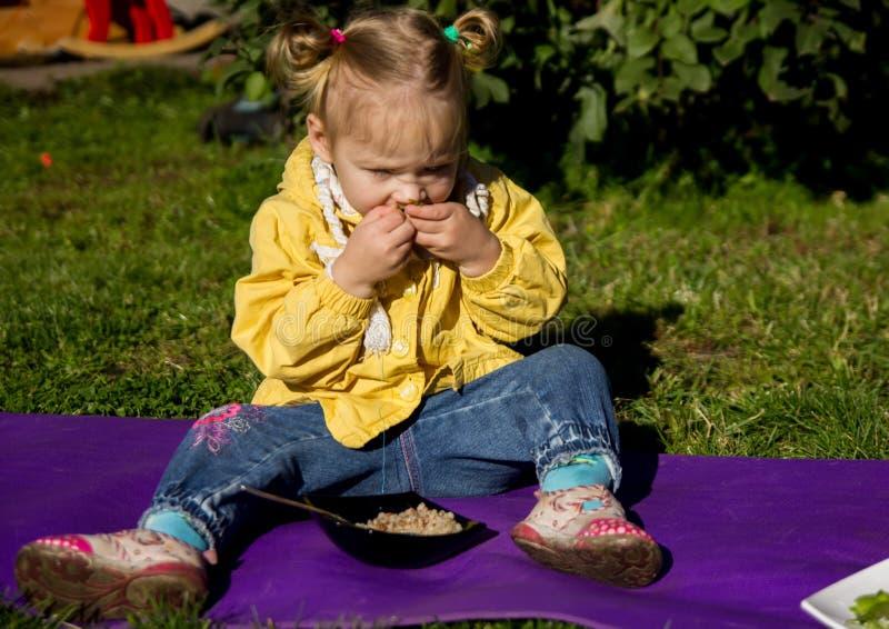Piccola ragazza affamata che si siede su un'erba e che mangia i piselli immagine stock