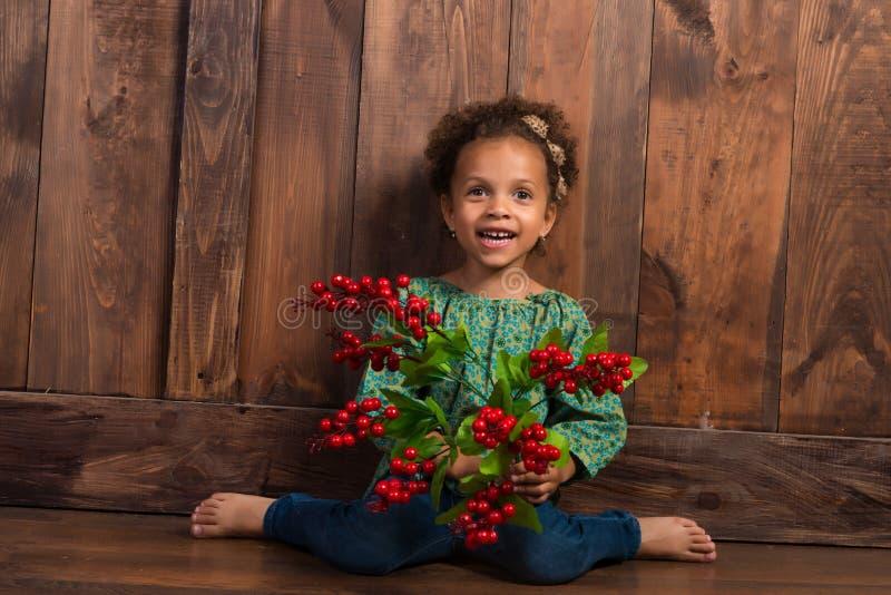 Piccola ragazza africana sorridente in camicia rurale con il mazzo di bacche su fondo della parete di legno marrone fotografia stock