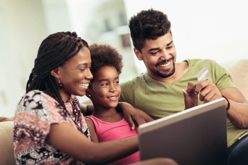 Piccola ragazza afroamericana sveglia ed i suoi bei giovani genitori che per mezzo del computer portatile immagini stock libere da diritti