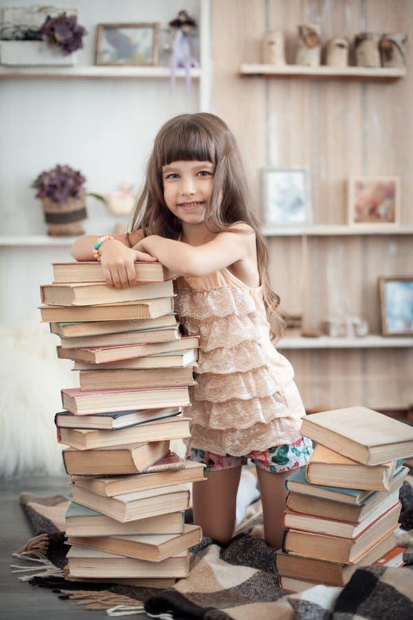 Piccola ragazza allegra con la pila di libri in biblioteca; immagini stock libere da diritti