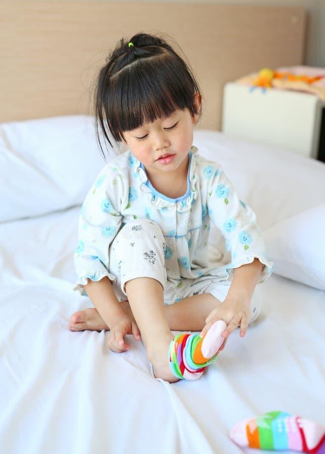 Piccola ragazza asiatica adorabile che prova a mettere i calzini sul letto immagini stock libere da diritti