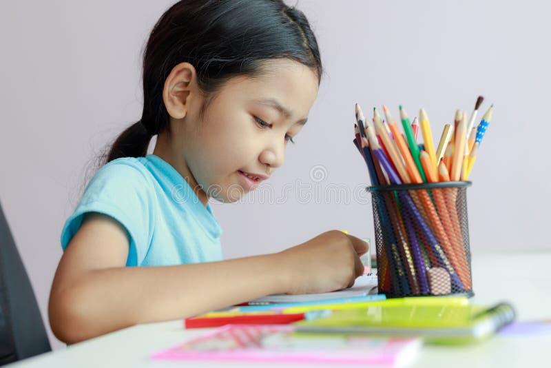 Piccola ragazza asiatica che mette facendo la matita di colore di uso di compito per attingere profondità di campo bassa del fuoc immagini stock