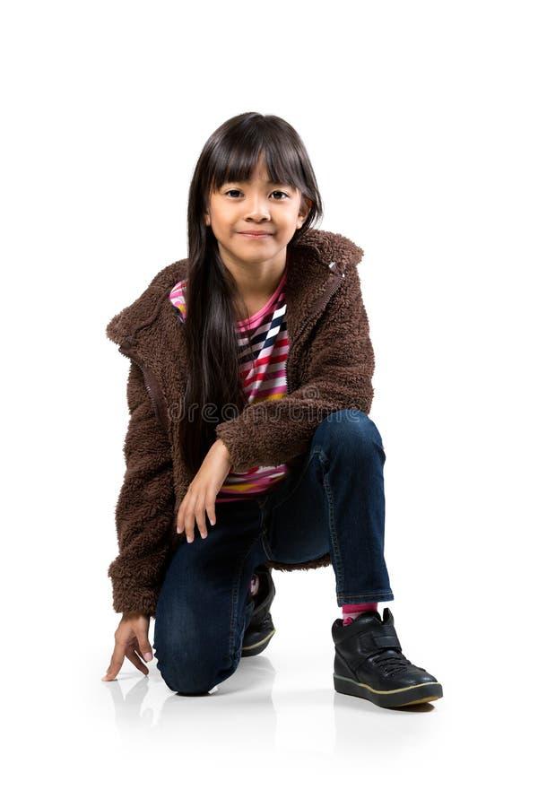 Piccola ragazza asiatica che si siede e che sorride sul pavimento immagine stock