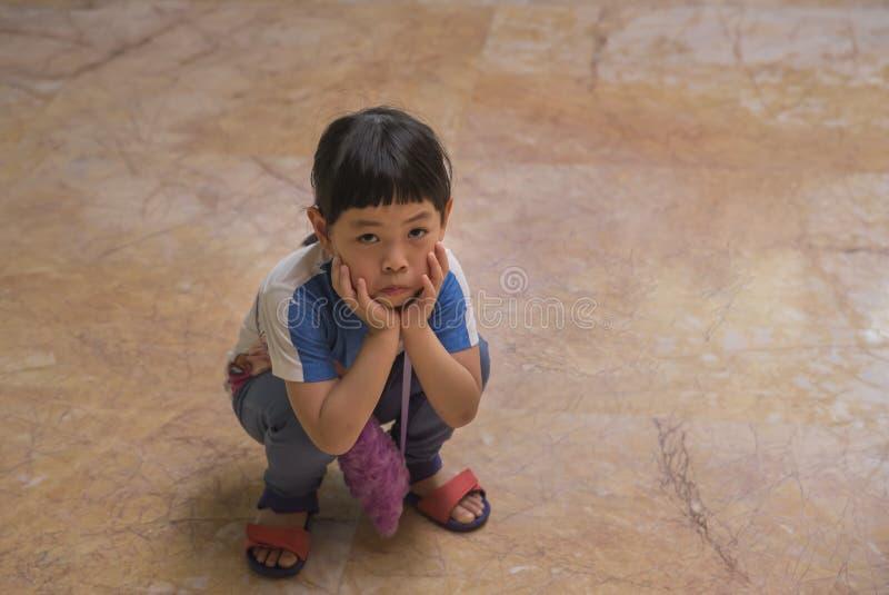 Piccola ragazza asiatica che si siede sul pavimento e che fa fronte infelice fotografia stock