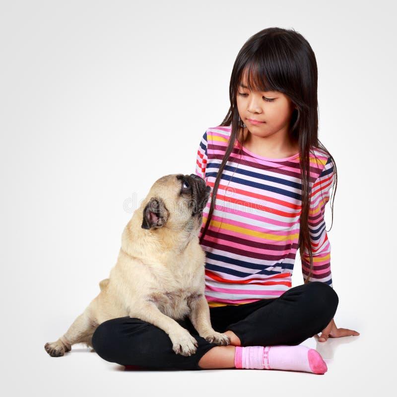 Piccola ragazza asiatica con il suo poco carlino fotografia stock