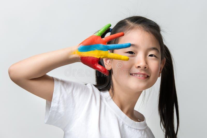 Piccola ragazza asiatica con le mani dipinte in pitture variopinte immagine stock